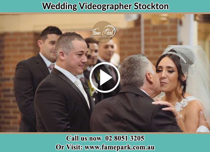 The Bride kiss by her father with the Groom waiting Stockton NSW 2295