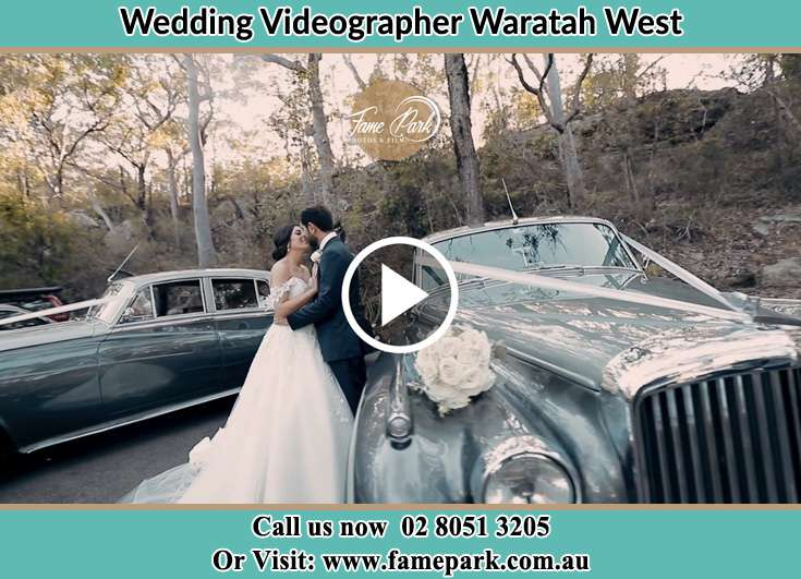 The new couple about to kiss near their wedding car Waratah West NSW 2298